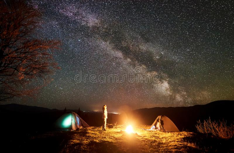 Night camping in mountains. Female hiker resting near campfire, tourist tent under starry sky royalty free stock photos