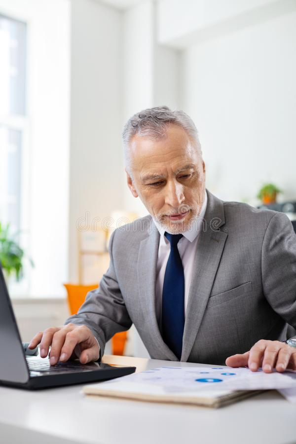 Peaceful concentrated old man in office costume inspecting information. Checking documents. Peaceful concentrated old man in office costume inspecting stock photo