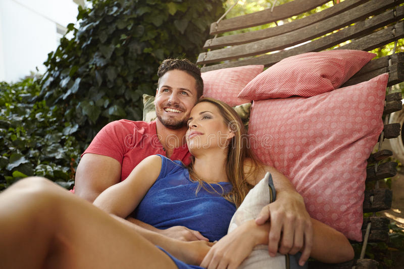 Peaceful couple relaxing on hammock in backyard. Portrait of happy and peaceful young couple relaxing on hammock in backyard. Man smiling with women looking away royalty free stock photography