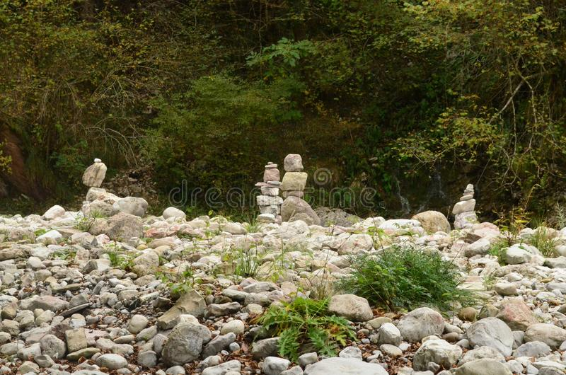Peaceful field of rocks with rocks stacked on each other. Peaceful field of rocks stacked on one-another with green background royalty free stock image