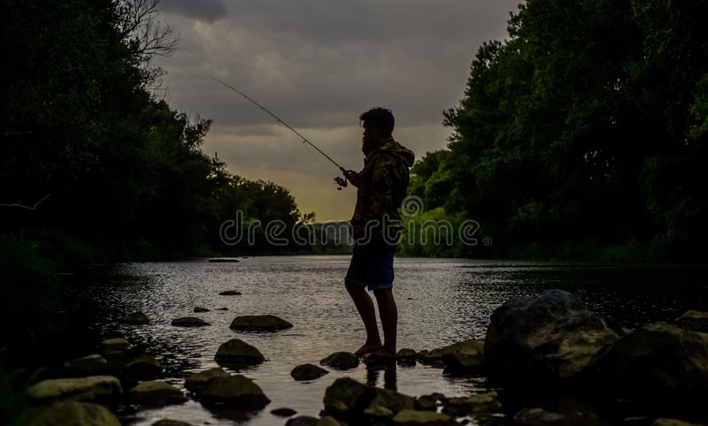 Peaceful fisherman. Fish farming pisciculture raising fish commercially. River lake lagoon pond. Trout farm. Fisherman. Alone stand in river water. Fisherman royalty free stock photos