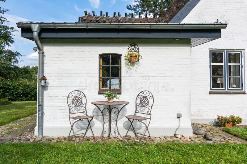 Peaceful garden with two chairs in front of whitewashed historic house in Northern Germany. Peaceful garden with two chairs in front of whitewashed historic reed royalty free stock photos