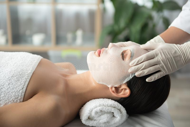 Peaceful girl getting facial skin care treatment royalty free stock photo