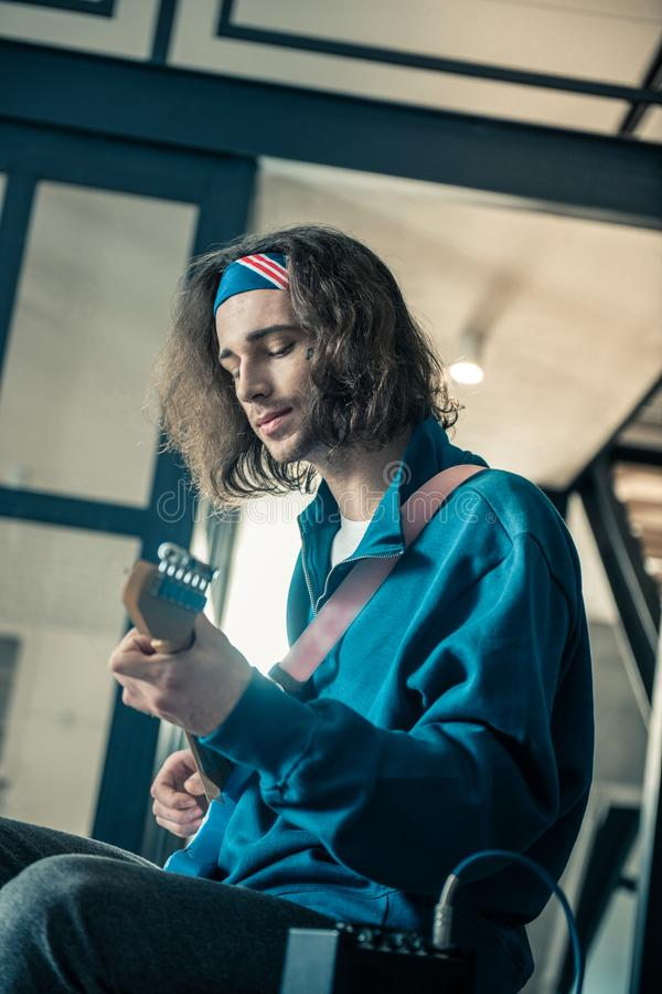 Peaceful handsome young man in bandana focusing on abilities of his instrument. Artist experimenting. Peaceful handsome young man in bandana focusing on royalty free stock photography