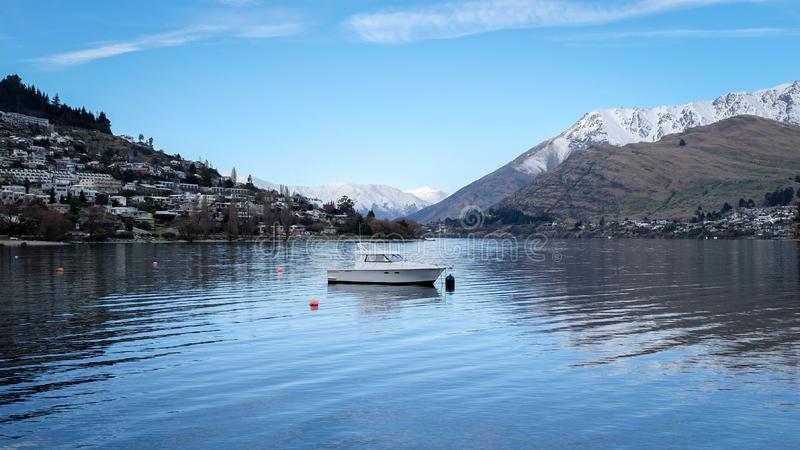Peaceful idyllic image of boat docked in the Queenstown Wakatipu Lake, New Zealand royalty free stock photos
