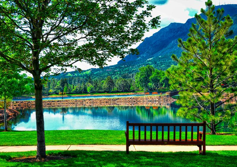 A Peaceful and Idyllic Image at the Broadmoor Hotel at Cheyene Mountain Lake and bench. Colorado Spring`s fife star hotel, the Broadmoor is located just beneath stock photo
