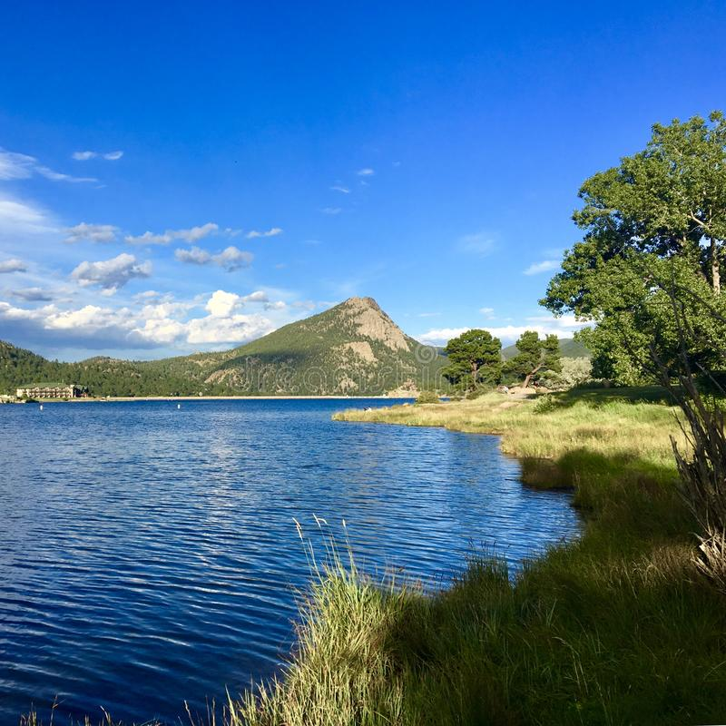 Peaceful lake with a single mountain in the background stock photos