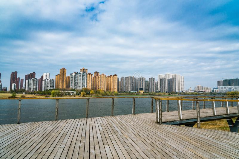 Peaceful lake view and urban building. A view of peaceful lake view and urban building with white clouds and blue sky stock photos