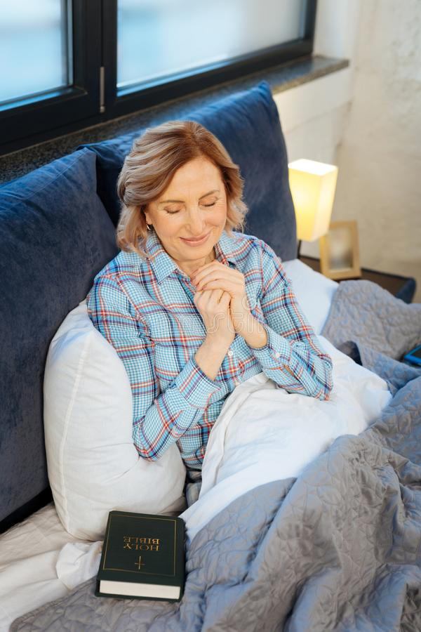 Peaceful light-haired woman praying in the morning stock image