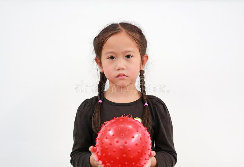 Peaceful little Asian child girl holding round silicone inflatable red knobby ball on white background stock photos