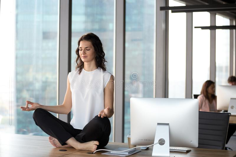 Peaceful businesswoman practice yoga sitting on table in office royalty free stock photo