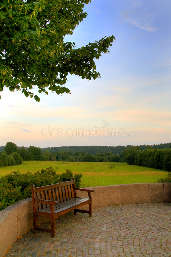 Peaceful parkbench. Parkbench in front of rural landscape royalty free stock photo