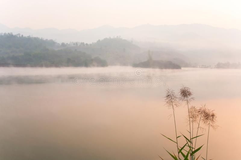 Peaceful place, Pa Khong Lake in morning light in winter season, soft mist covers on the lake and mountains. Scenic landscape of. Dien Bien, Vietnam. Warm tone royalty free stock photos