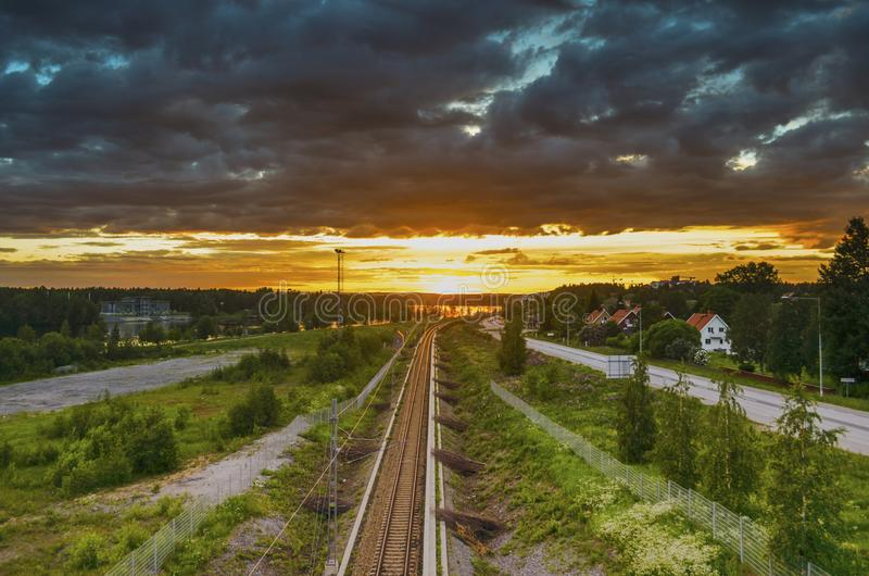 Peaceful reflection of sunlight on moving cloud and leading train line to the orange horizon in beautiful summer day stock photos