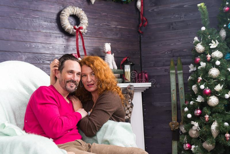 Romantic couple hugging and enjoying New Year at home. Peaceful relaxed middle aged women sitting next to her bearded husband and smiling while hugging him royalty free stock photography