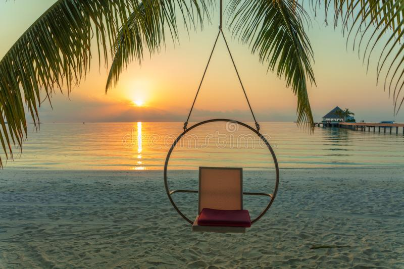 Peaceful Round Swing over paradise sandy beach with Ocean Water stock photo
