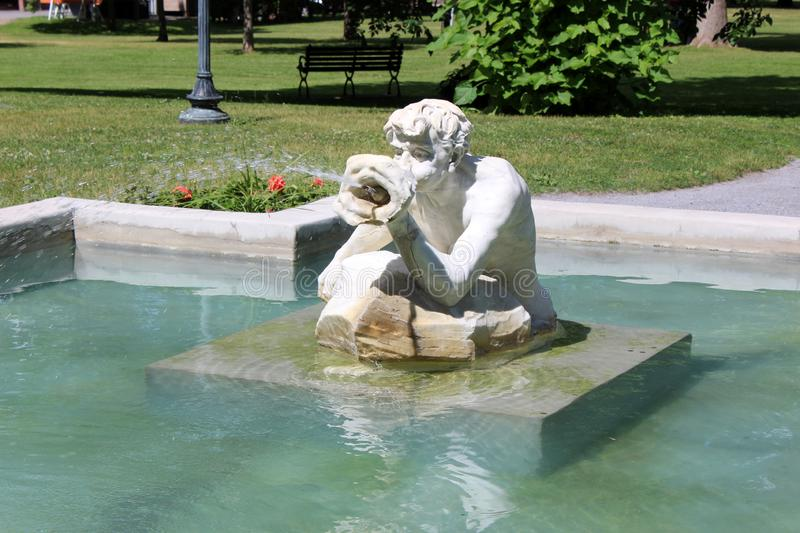 Peaceful scene with marble fountain and statue of `Spit and Spat` leading into Congress Park, Saratoga, New York, 2018 royalty free stock image