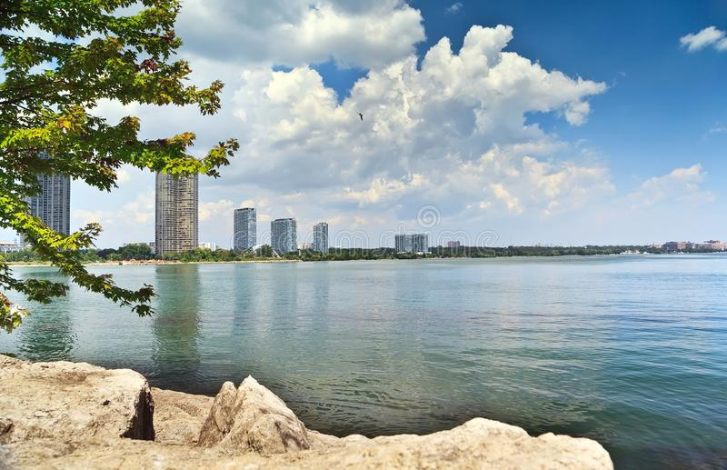 Riverbank. Peaceful scenic view of riverbank with high rise buildings and white clouds on blue sky stock photos