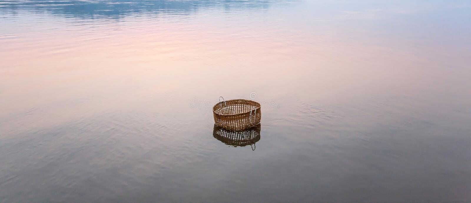 Peaceful serene by river, a bamboo basket is dipping in the Mekong River on winter morning, still life in rural Laos stock photo