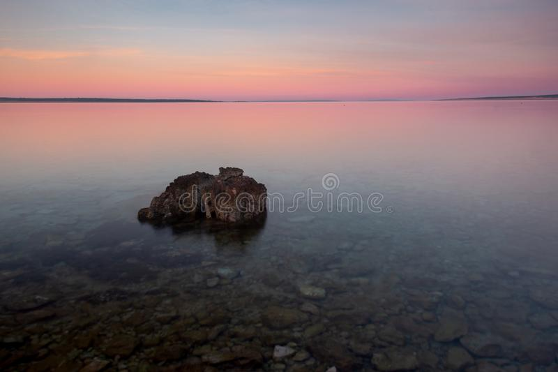 Sunrise Croatia Beach with Pastel Color sky and Rock in Foreground royalty free stock photography