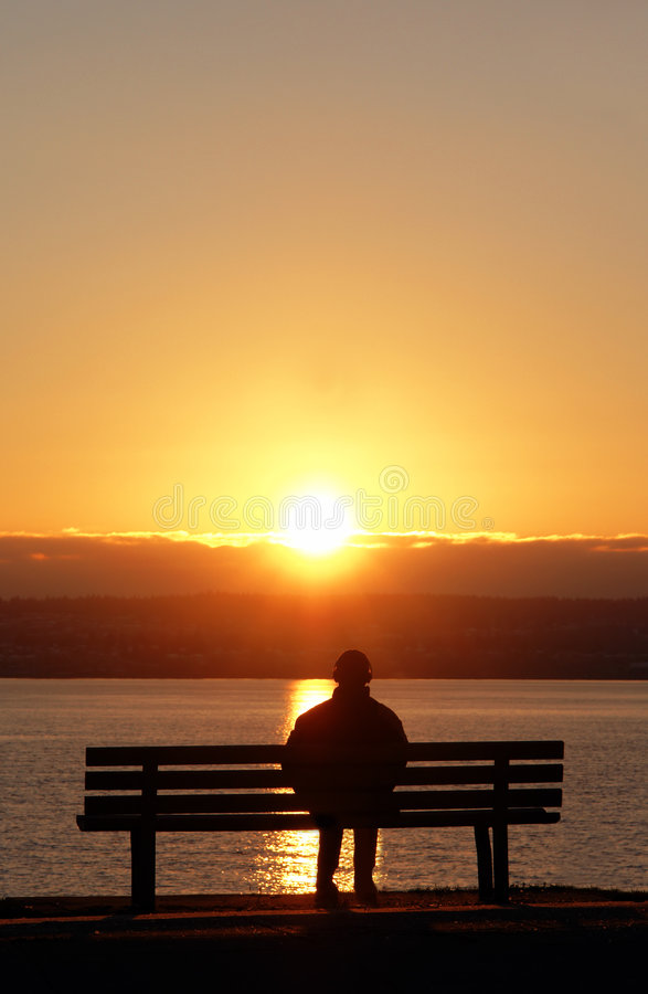 Peaceful Sunset. Man listening to tunes while enjoying a sunset royalty free stock photo