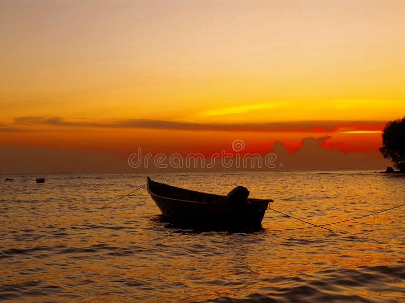 A peaceful sunset over a boat in Port Dickson royalty free stock photos