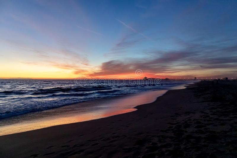 Sunset over the ocean with pier in the background. Peaceful sunset over the ocean and beach showing the Huntington Beach pier in the distance royalty free stock images