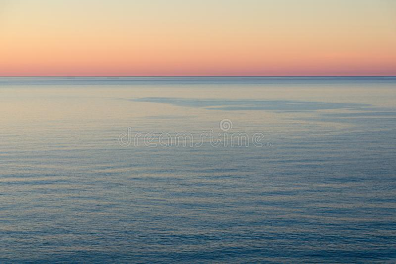 Peaceful sunset by the sea. Calm water, bright sky. stock photography