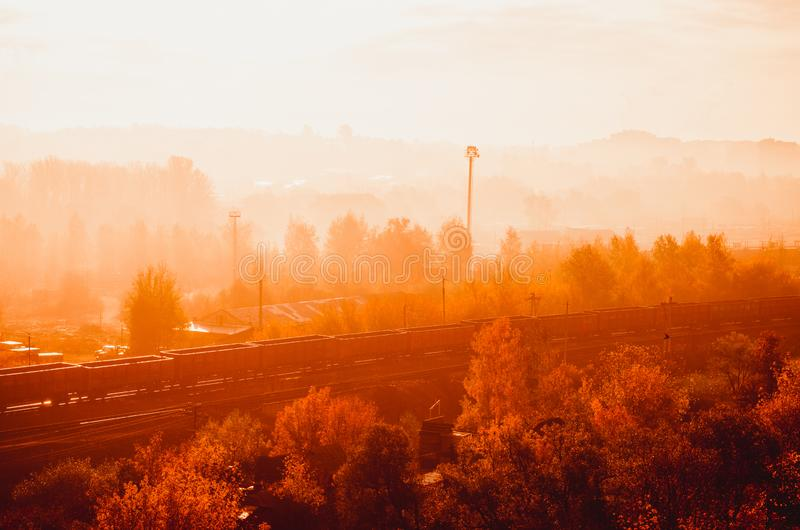 Peaceful sunset view with train and forest in a small town. Seasonal scenery with warm sunlight royalty free stock photos
