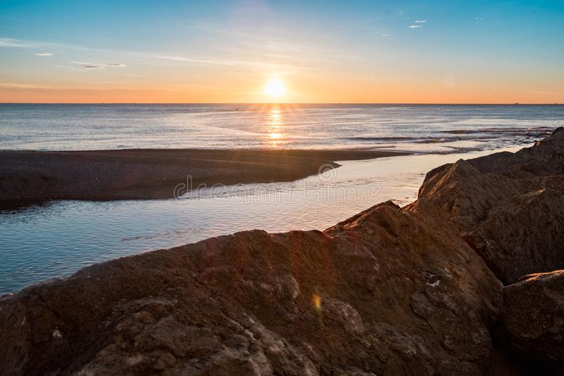 Peaceful view of sun rising over calm sea from rock pier in barcelona city at besos estuary stock image