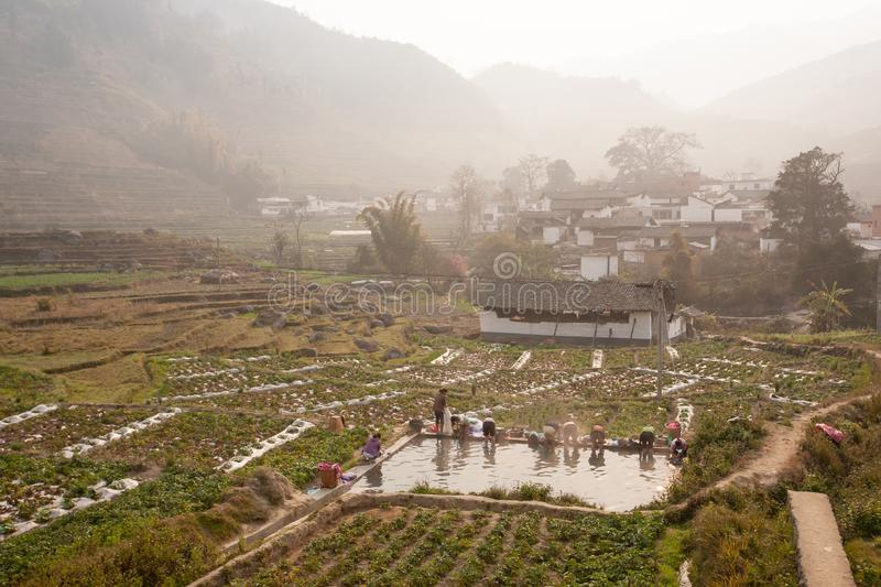 Peaceful village. Scenic ancient village landscape, a group of chinese woman washing at the old pool in potato's field in the stock photos