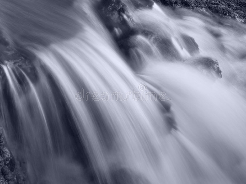Peaceful Waters. Peaceful waterfall flowing over rocks, black and white royalty free stock photography
