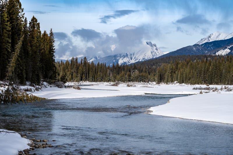 Peaceful winter scene along the Kootenay River in Kootenay National Park British Columbia. Pillows of snow along the riverbaks royalty free stock image