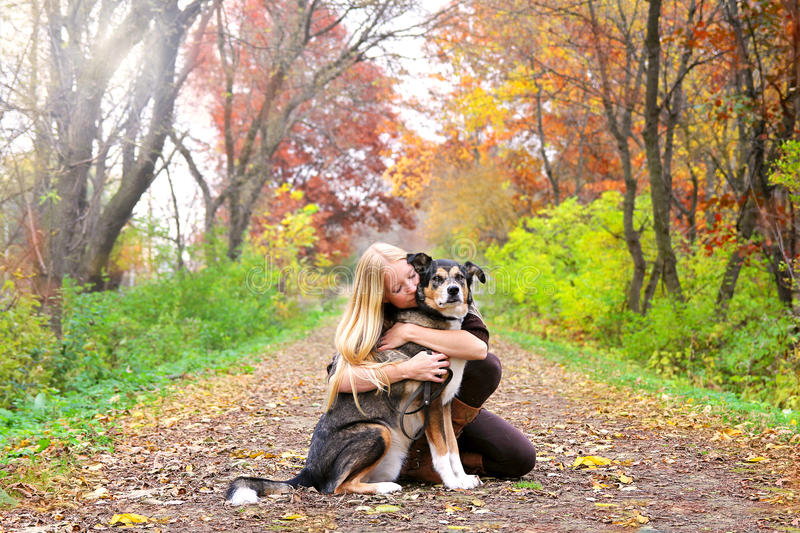 Peaceful Woman Hugging Pet Dog While on Walk in Woods. A happy and peaceful young woman is hugging her German Shepherd mix breed dog, as the rest while on a walk stock image