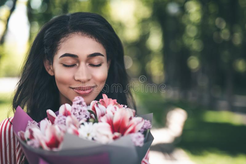 Peaceful woman smiling and enjoying the smell of flowers royalty free stock photo