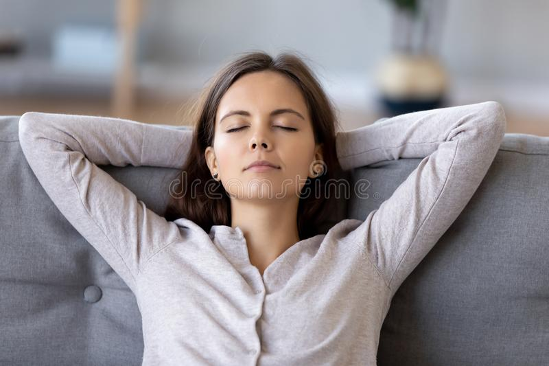 Peaceful young woman with hands behind head relaxing at home. Sitting on comfortable sofa in living room, carefree girl with closed eyes resting, daydreaming royalty free stock photo