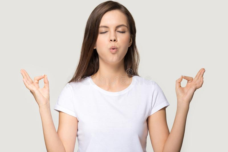 Calm millennial girl meditating in studio breathing deep stock image