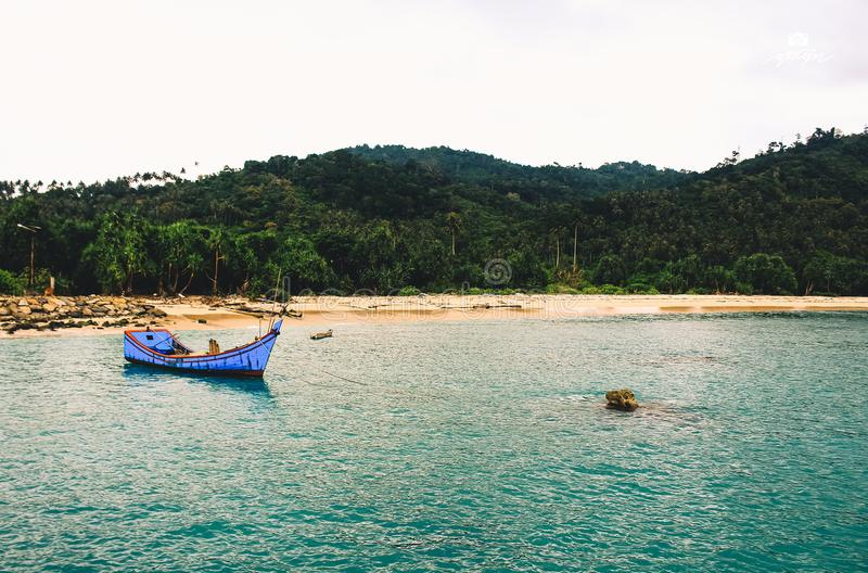 Peacefull blue shore in Aceh. Blue peacefull shore boat hill trees rock sand sky horizon landscape jungle horizon cloud mountain lhoksukon aceh indonesia royalty free stock photos
