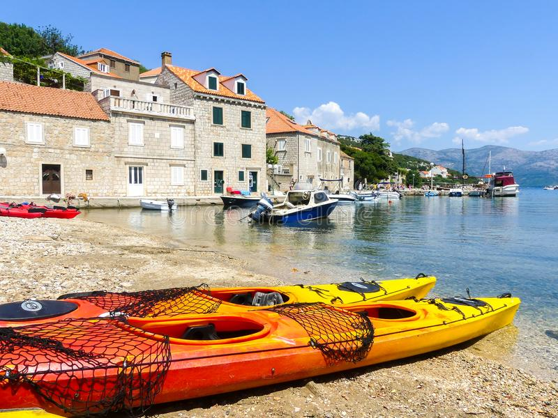 Peacefull coastal scene on the Dalmaitia coast of Croatia with sport kayaks boats and holiday houses. Lopud island, Elephiti islands, Croatia -August 6 2018 royalty free stock photos