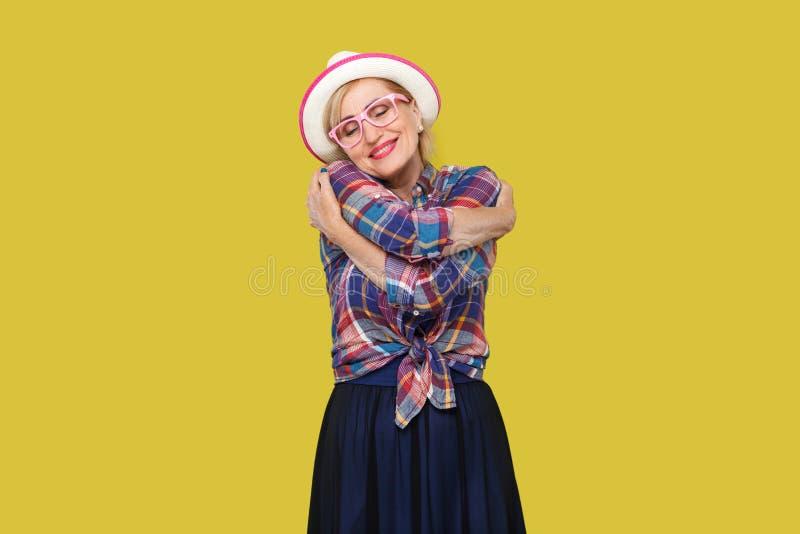 peacful愉快的现代时髦的成熟妇女画象便装样式的与帽子,镜片身分,拥抱与闭合 图库摄影
