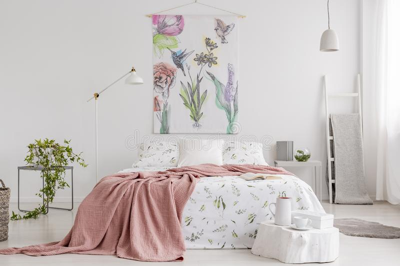 Peach blanket and white with green pattern linen on bed in a natural bright bedroom interior. Tapestry with colorful flowers and birds on the back wall. Real royalty free stock photography