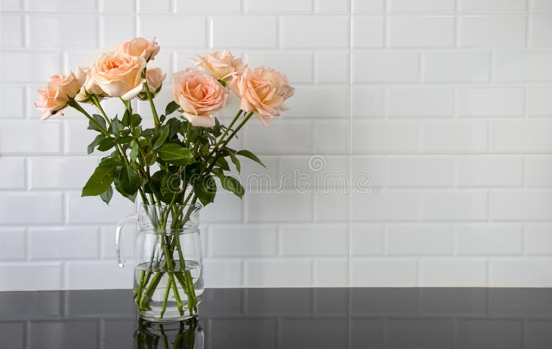 Peach color roses in a glass jug. Beautiful peach color roses in a glass jug on black granite kitchen counter and white tile background, vase, bouquet, flower royalty free stock photography