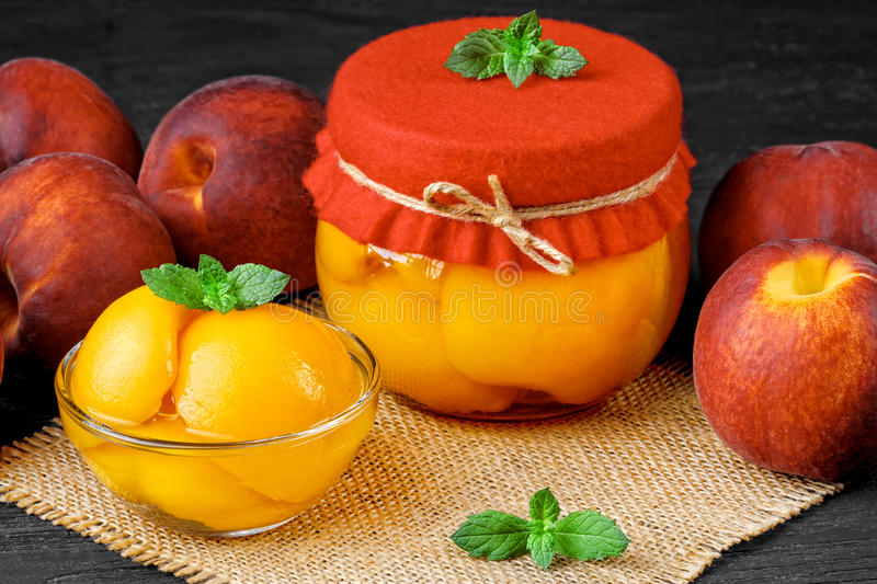 Peach compote. With half peaches in glass jars on an old black wooden tableselective focus stock image