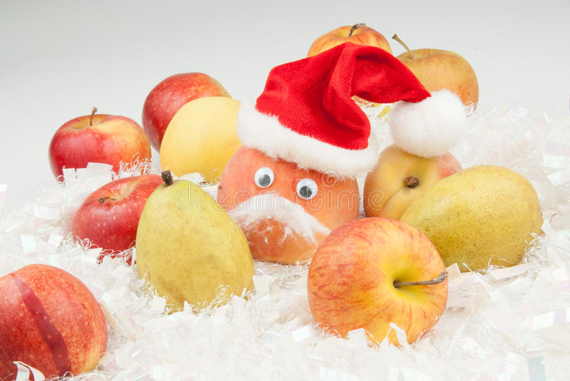 Peach with eyes and Santa Clause hat and mustache. On the white like a snow decor is several fruits and one red color peach with Santa Clause hat on the top of stock images