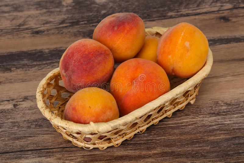 Peach heap in the wooden basket. Ripe Peach heap in the wooden basket stock photography