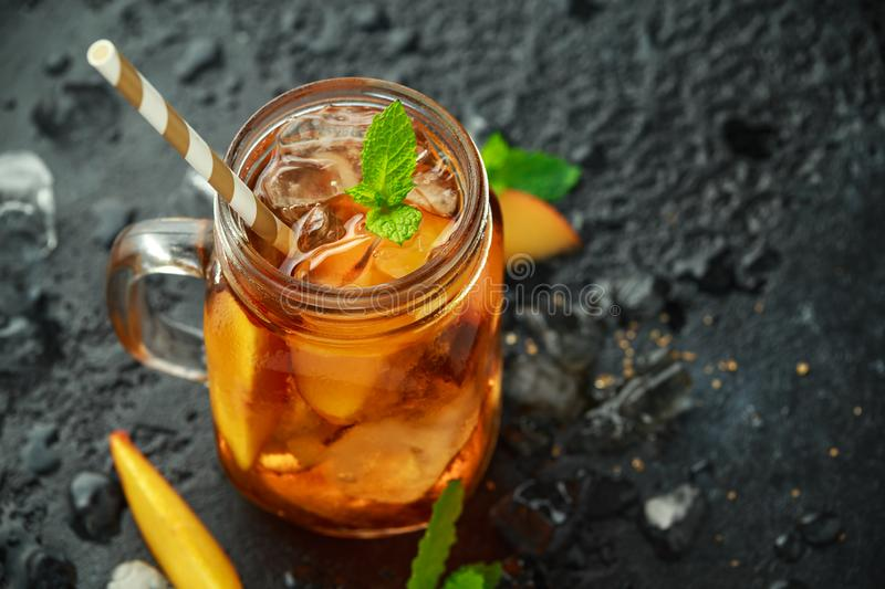 Peach Ice tea with mint in glass jar, on rustic black background. summer fruit cold drinks royalty free stock image
