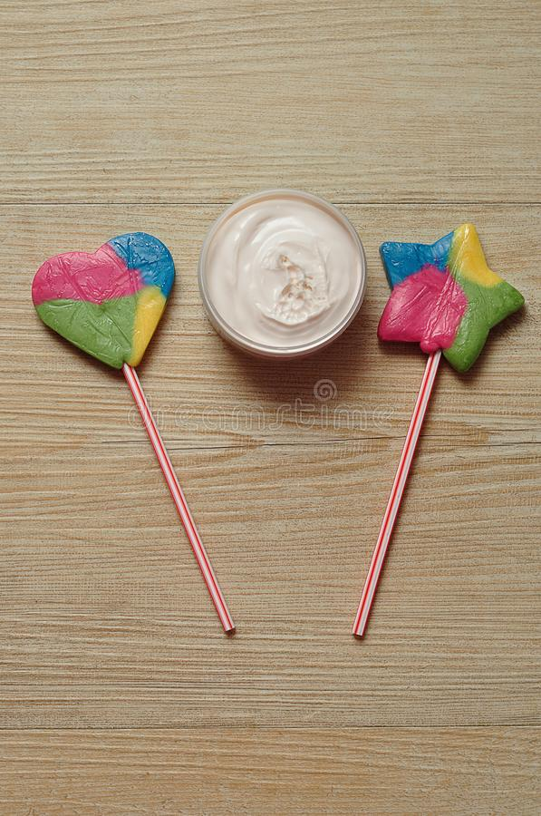 A peach jar of body lotion displayed with a star shape lollipop and a heart shape lollipop stock image