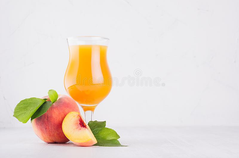 Peach juice in elegance glass with juicy piece peaches on light white wood table, copy space. stock photography