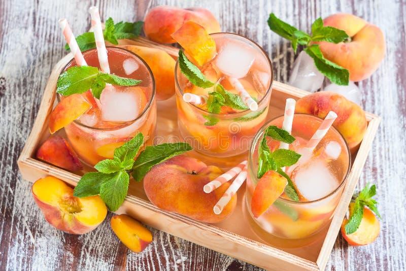 Peach lemonade. Homemade lemonade with ripe flat saturn-shaped peaches and fresh mint royalty free stock image
