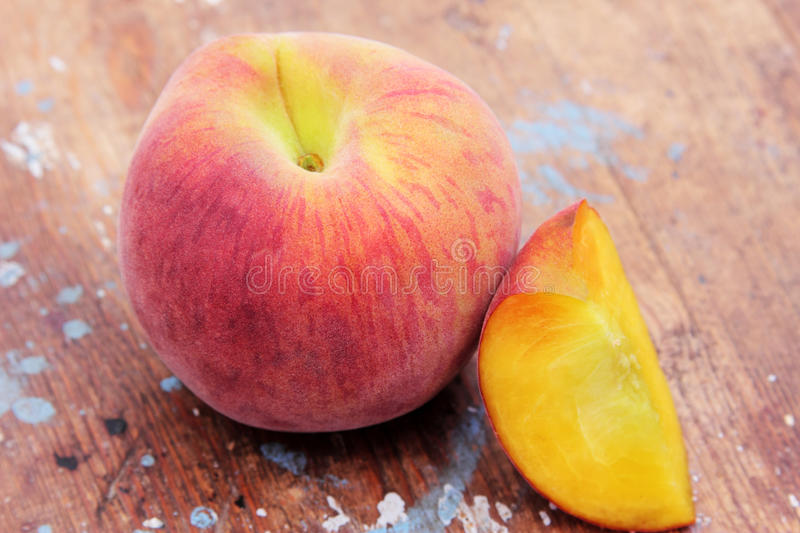 Peach. One peach and slice on wooden background royalty free stock images